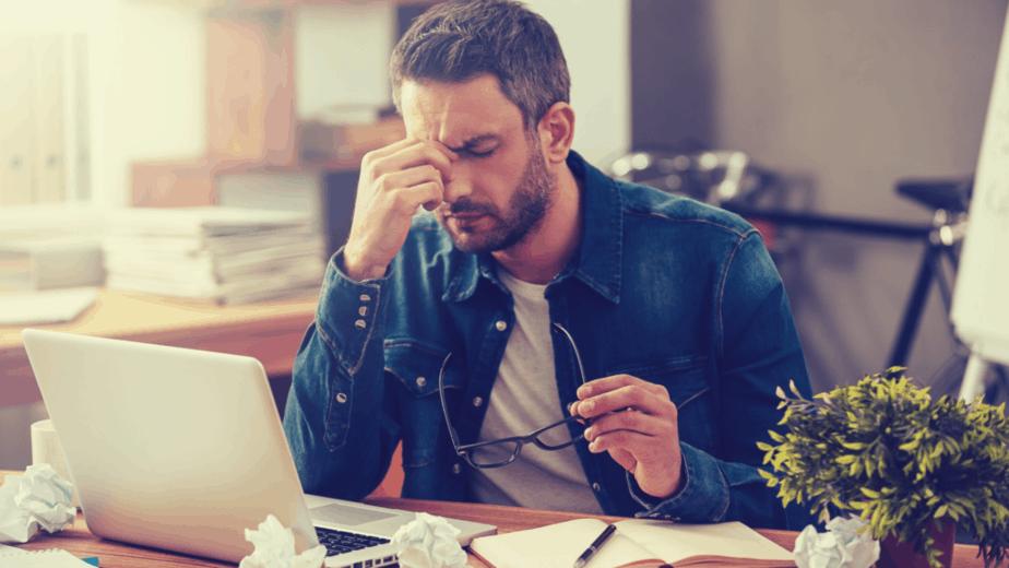 גבר יושב מול מחשב, עייף, לא מרוכז ומתוסכל